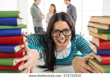 Portrait of a beautiful funny student girl sitting and shouting among the many book's in the foreground. Looking at camera. - stock photo