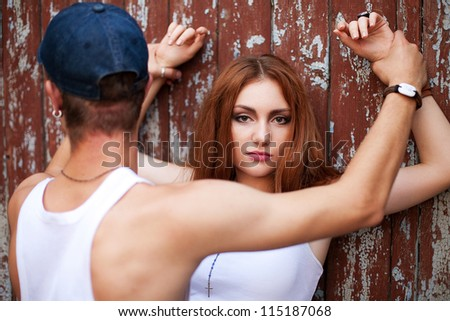 portrait of a beautiful ginger girl standing with a man over wooden background. boy holding girl's hands. outdoor shot - stock photo