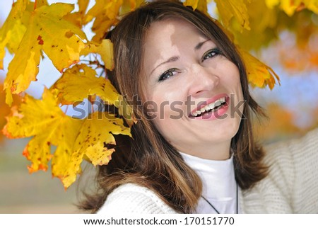 portrait of a beautiful girl among the yellow leaves in autumn