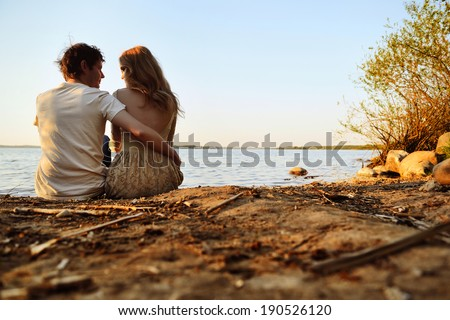 portrait of a beautiful girl and a guy sitting near  the river at sunset - stock photo