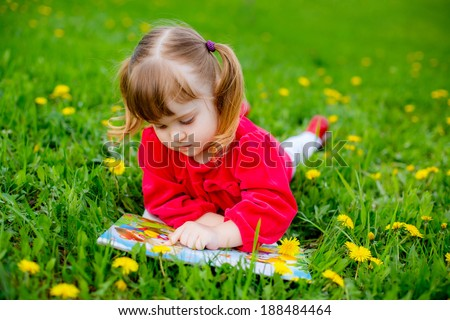 portrait of a beautiful  girl. baby lying on the grass and reading a book - stock photo