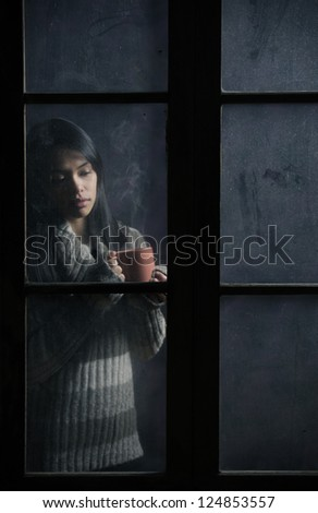 Portrait of a beautiful girl behind window with a cup of coffee or tea