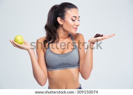 Portrait of a beautiful girl choosing between apple or chocolate isolated on a white background - stock photo