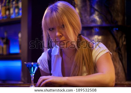 portrait of a beautiful girl drinking in a bar
