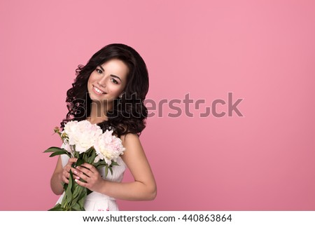 Portrait of a beautiful girl holding a bouquet of pale pink peonies. Smiling young woman with flowers isolated on pink background with copyspace for your text - stock photo