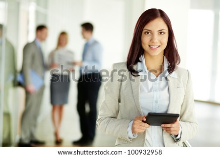 Portrait of a beautiful girl holding a tablet computer and looking at camera - stock photo