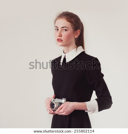 portrait of a beautiful girl in a black dress with camera in hand - stock photo