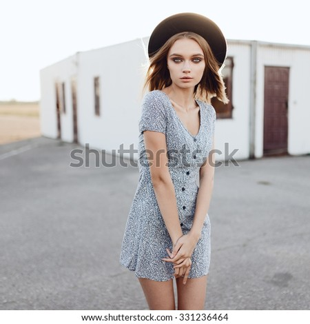 Portrait of a beautiful girl in a dress and hat against the sun
