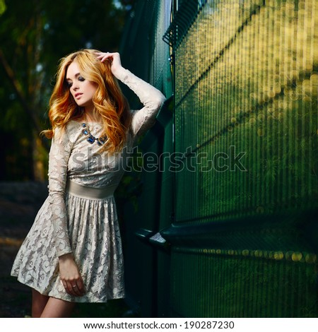 portrait of a beautiful girl in a dress near the fence sunlit - stock photo
