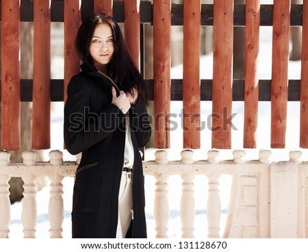 Portrait of a beautiful girl in a fashionable coat the fence