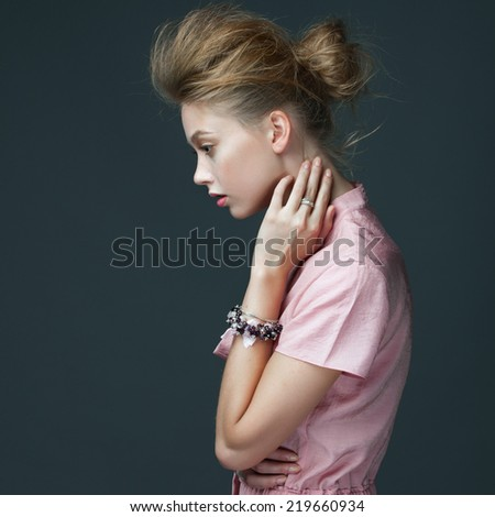 Portrait of a beautiful girl in a pink dress posing in studio on a gray background - stock photo