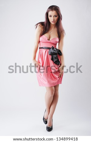 Portrait of a beautiful girl in a pink gauzy dress on light background/ Girl shows emotion, anger, anxiety, smile, joy