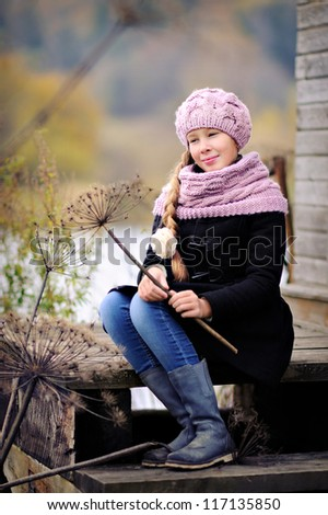 Portrait of a beautiful girl in a pink hat and scarf. Long hair. The child sits on the porch - stock photo
