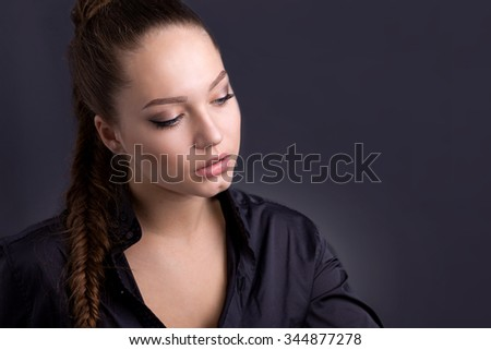 Portrait of a beautiful girl in a simple style, on a gray, rough background