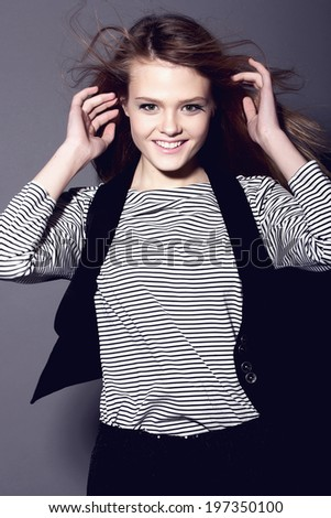 Portrait of a beautiful girl in a striped t-shirt, smiling in studio - stock photo
