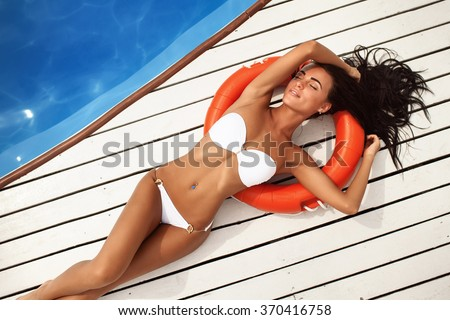 portrait of a beautiful girl in a white bathing suit lying by the pool. Top view - stock photo