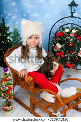 Portrait of a beautiful girl in a white cap and knit sweater sitting in wicker sleigh holding a bear on the background of Christmas decorations