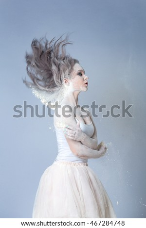Portrait of a beautiful girl in a white dress dancing with flour in the Studio
