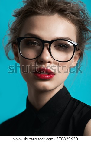 Portrait of a beautiful girl in round glasses on a blue background in the studio, the concept of beauty - stock photo