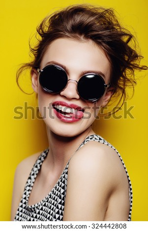 Portrait of a beautiful girl in round glasses on a yellow background in the studio  - stock photo