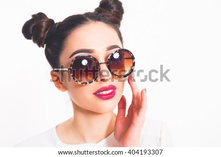 Portrait of a beautiful girl in round glasses on white background in the studio.Attractive, beauty and fashion concept.Beauty Fashion model brunette girl wearing stylish sunglasses.Sexy woman portrait