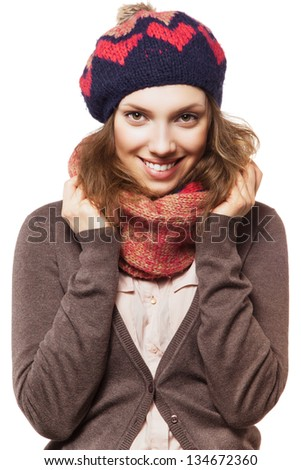 Portrait of a beautiful girl in scarf and beret with hands next to her head, looking at camera and smiling