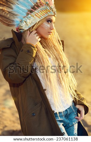 Portrait of a beautiful girl in style of the American Indians on a sunset. Western style. Jeans fashion. - stock photo