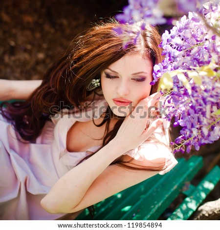Portrait of a beautiful girl in stylish dress, sitting at the park among flowers - stock photo