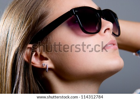 Portrait of a beautiful girl in sunglasses on a gray background - stock photo
