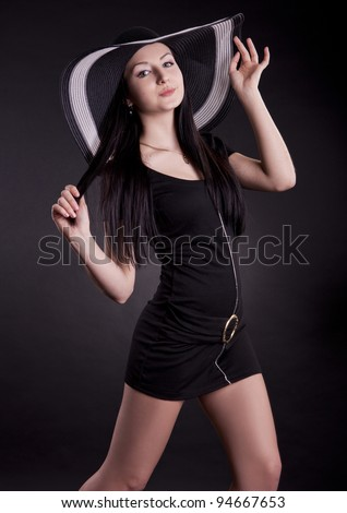 portrait of a beautiful girl in the hat on a black background - stock photo
