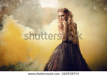 Portrait of a beautiful girl in the lush dress. Fairy tale about princess or witch, walking through the misty forest. - stock photo