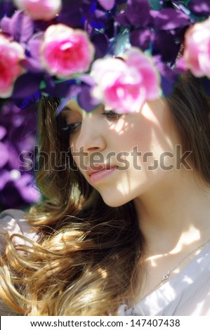 portrait of a beautiful girl in the tea roses and blue leaves