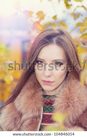 portrait of a beautiful girl in the yellow autumn leaves - stock photo