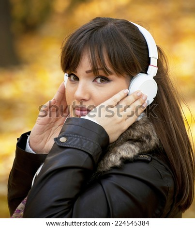 Portrait of a beautiful girl listening to music in autumn park - stock photo