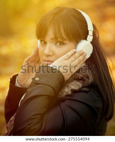 Portrait of a beautiful girl listening to music in autumn park
