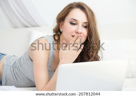 Portrait of a beautiful girl near notebook on the bed