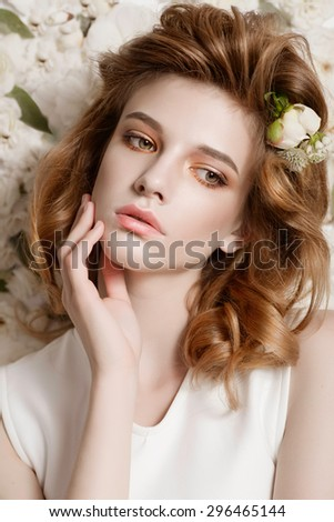 Portrait of a beautiful girl on a background of delicate white flowers, the concept of beauty and health - stock photo