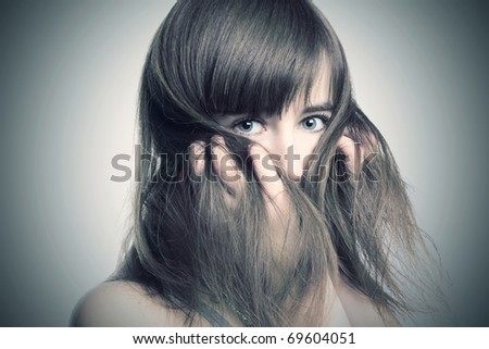 Portrait of a beautiful girl on a gray background - stock photo