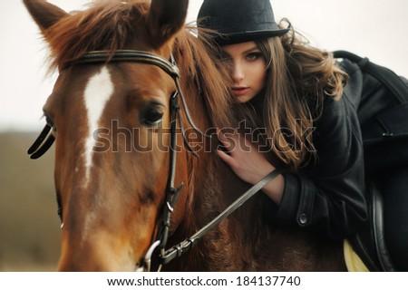 portrait of a beautiful girl on horseback - stock photo