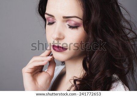 Portrait of a beautiful girl on studio background. Close-up lips and eyes. Make-up and hairstyle concept.