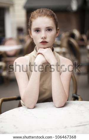 portrait of a beautiful girl on the street in a cafe - stock photo