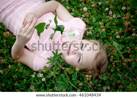 Portrait of a beautiful girl outdoors sitting on grass with flowers