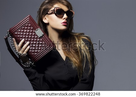 portrait of a beautiful girl posing in studio in black shirt, blue jeans and fashion sunglasses, holding Burgundy handbag . The concept of stylish and sexy women. perfect skin and body - stock photo