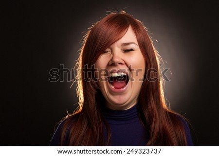 Portrait of a beautiful girl screaming on a black background