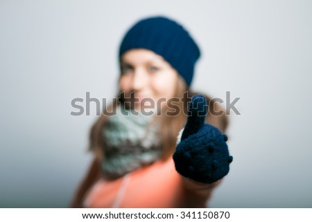 Portrait of a beautiful girl showing thumbs up sign in the winter, warm clothing. hipster, on a gray background - stock photo