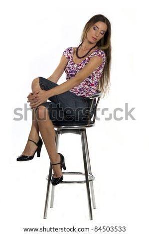 Portrait of a  beautiful girl sits on the bar stool on a white background closeup