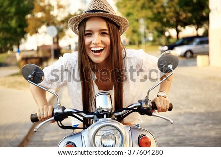 Portrait of a beautiful girl sitting on a silver retro scooter, smiling and looking at the camera - stock photo