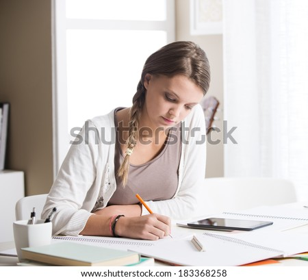 Portrait of a beautiful girl studying at home - stock photo
