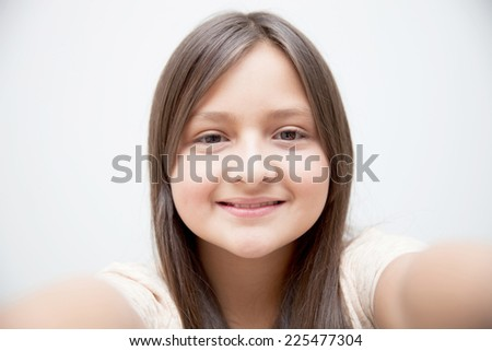 Portrait of a beautiful girl taking a selfie - stock photo
