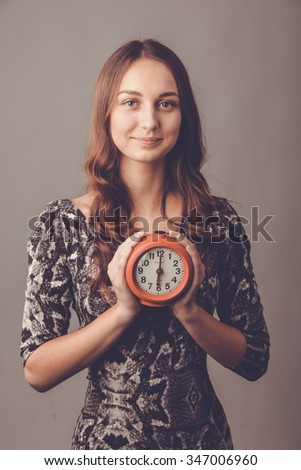 Portrait of a beautiful girl. Toned image. A young woman holding a clock alarm. At six in the evening hours - this is the end of the working day. Portrait of smiling woman in studio. - stock photo